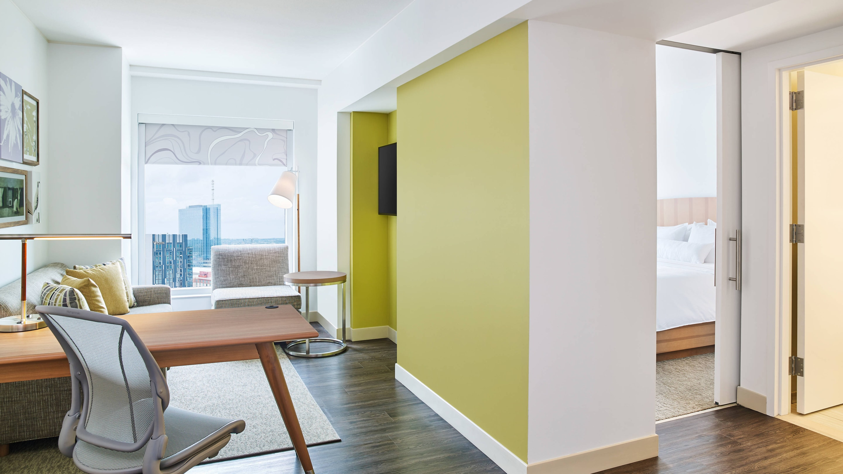 Guestroom featuring workdesk and yellow wall with hallway