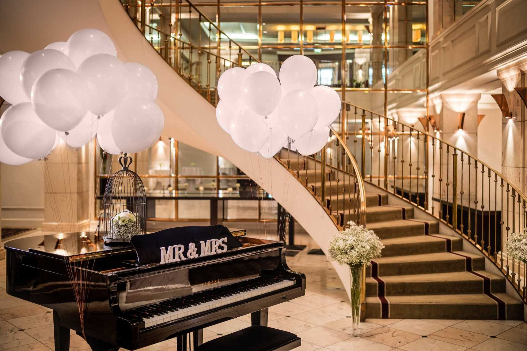 Piano with balloons and stair case