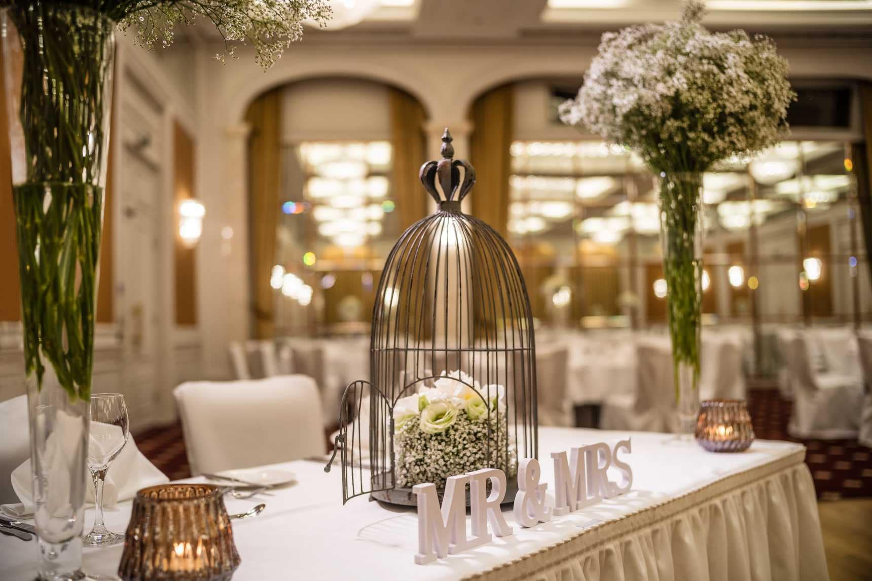 Reception table with a birdcage, flowers and wooden letters