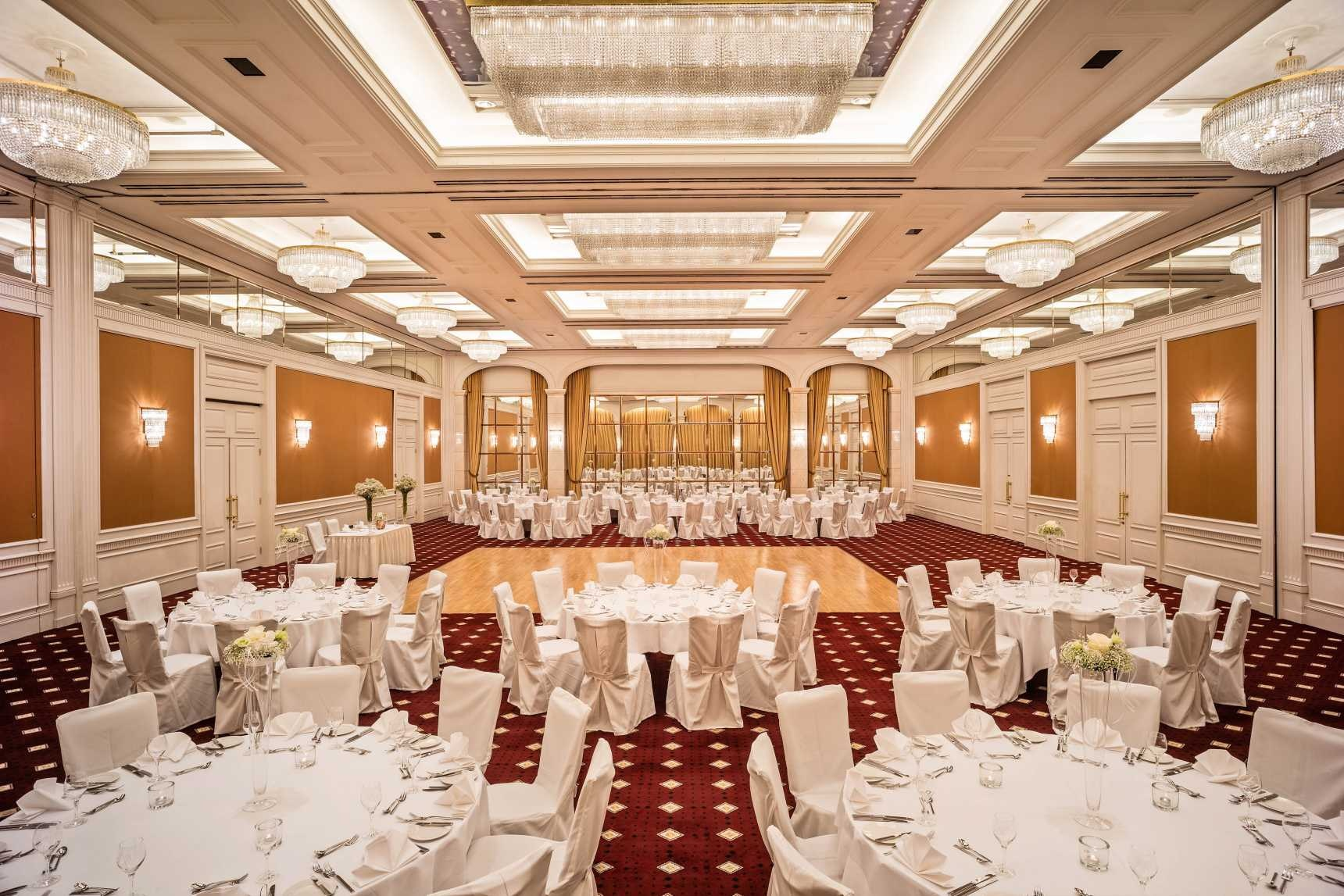 Large ballroom with round tables in white linen, dance floor in the middle