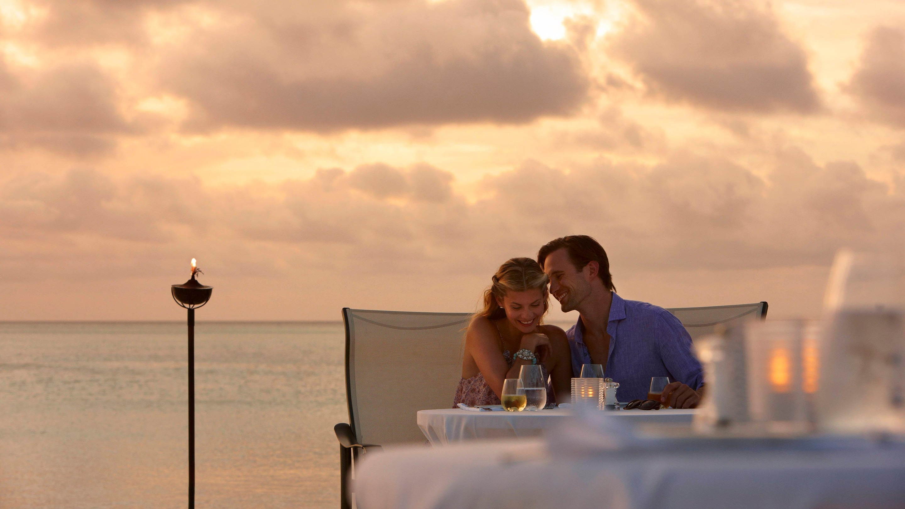 A couple enjoying an intimate moment dining on the beach with sun backlit clouds in the background.