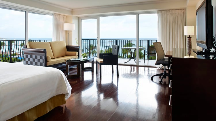 Suit living area with hardwood floors assorted furniture and a view of the balcony.
