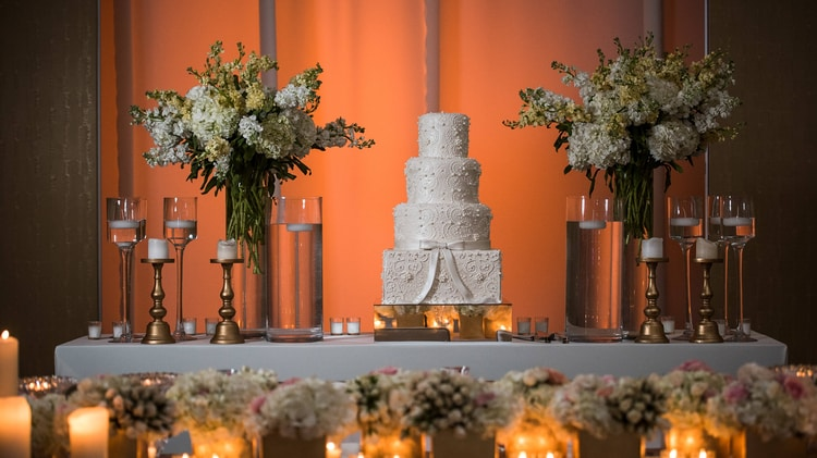 Wedding cake on table between white floral arrangements