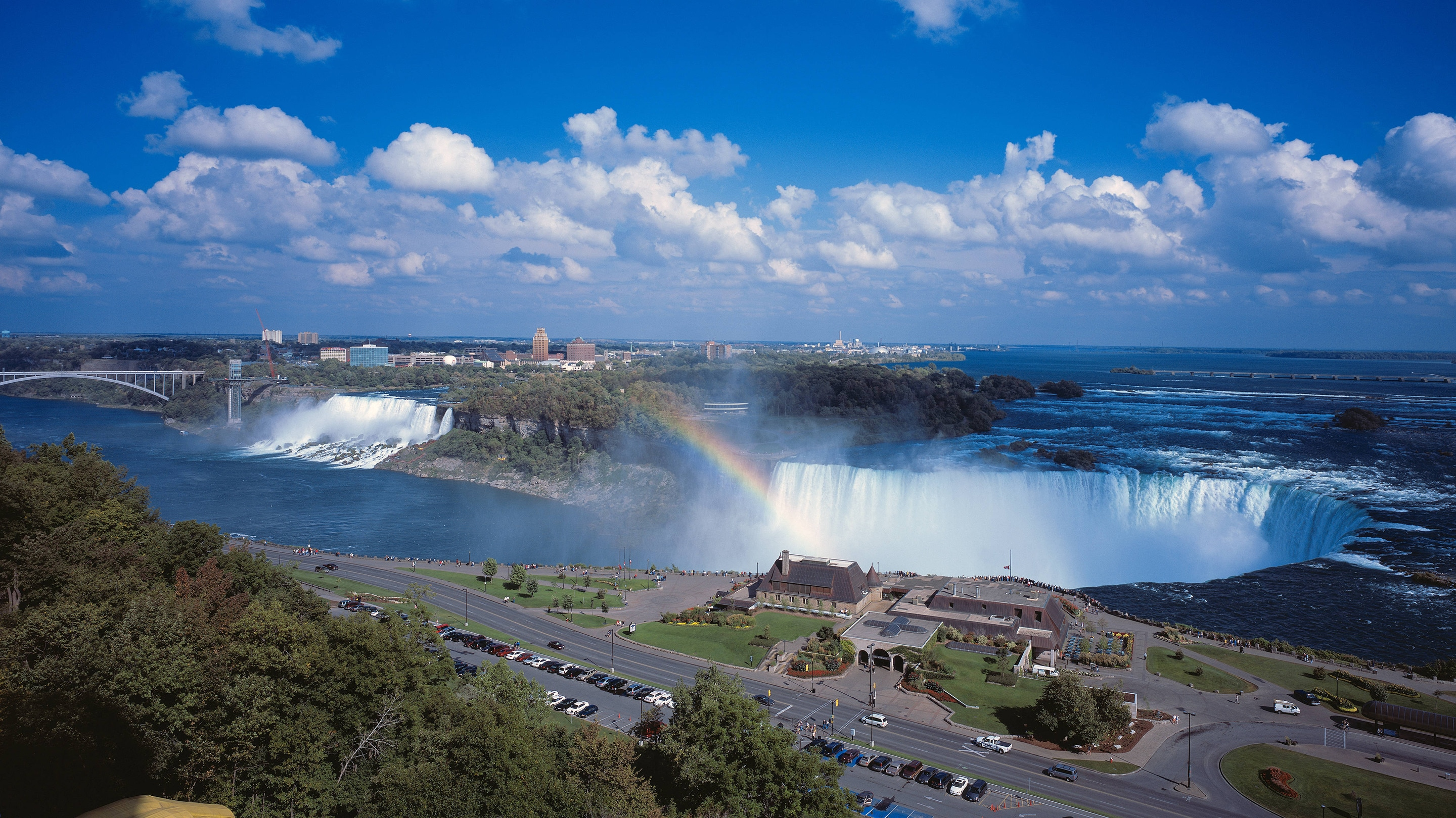 view of the falls with a rainbow and puffy clouds