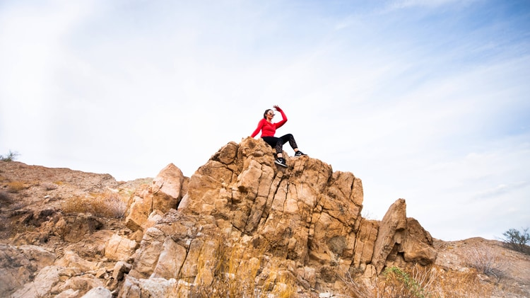 A woman sitting atop a rocky outcropping near a hiking trail.