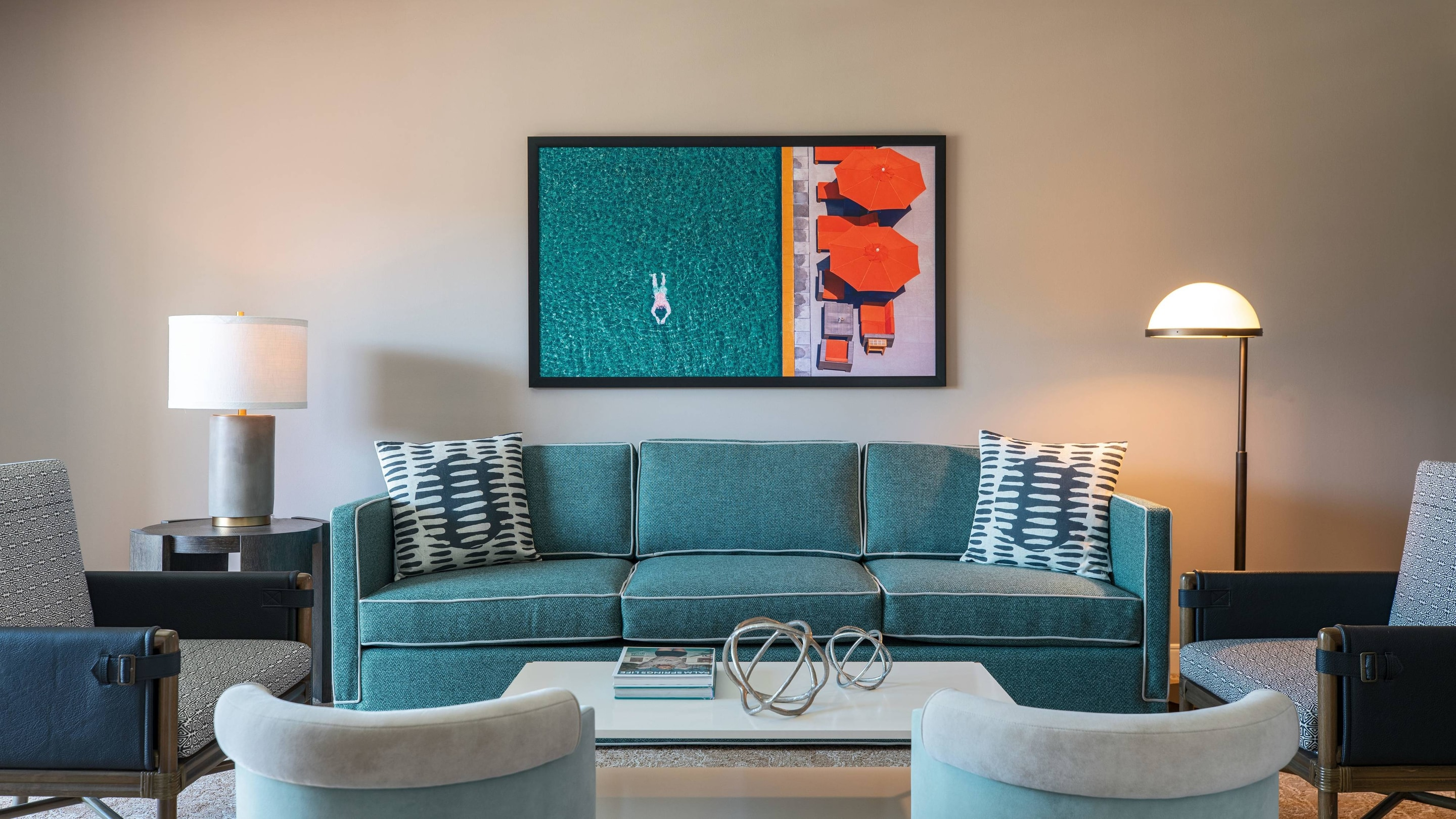 Assorted living area seating focusing on a three-cushion, teal green sofa and wall art.