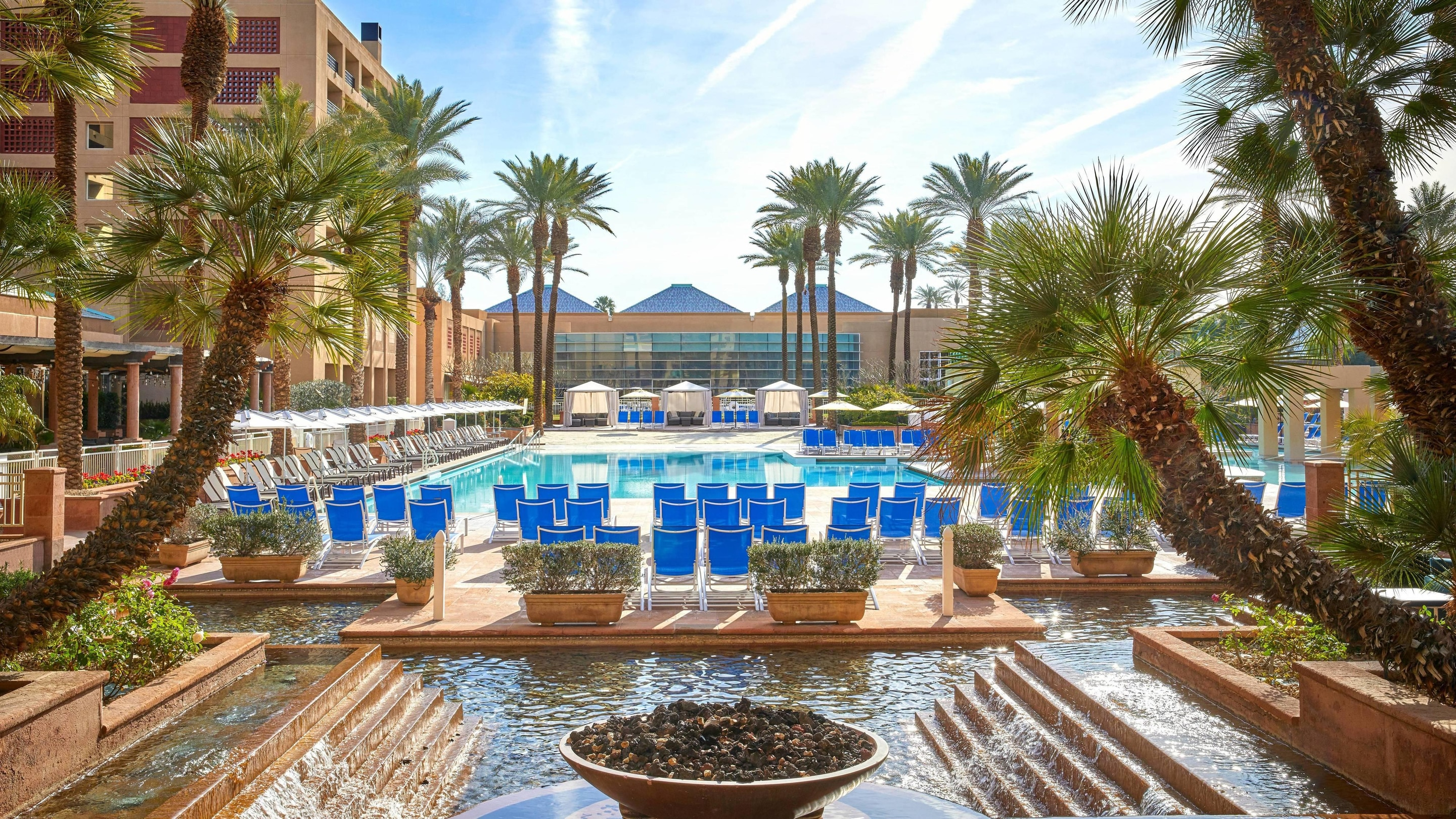 An expansive outdoor pool surrounded by palm trees and blue fabric chairs.