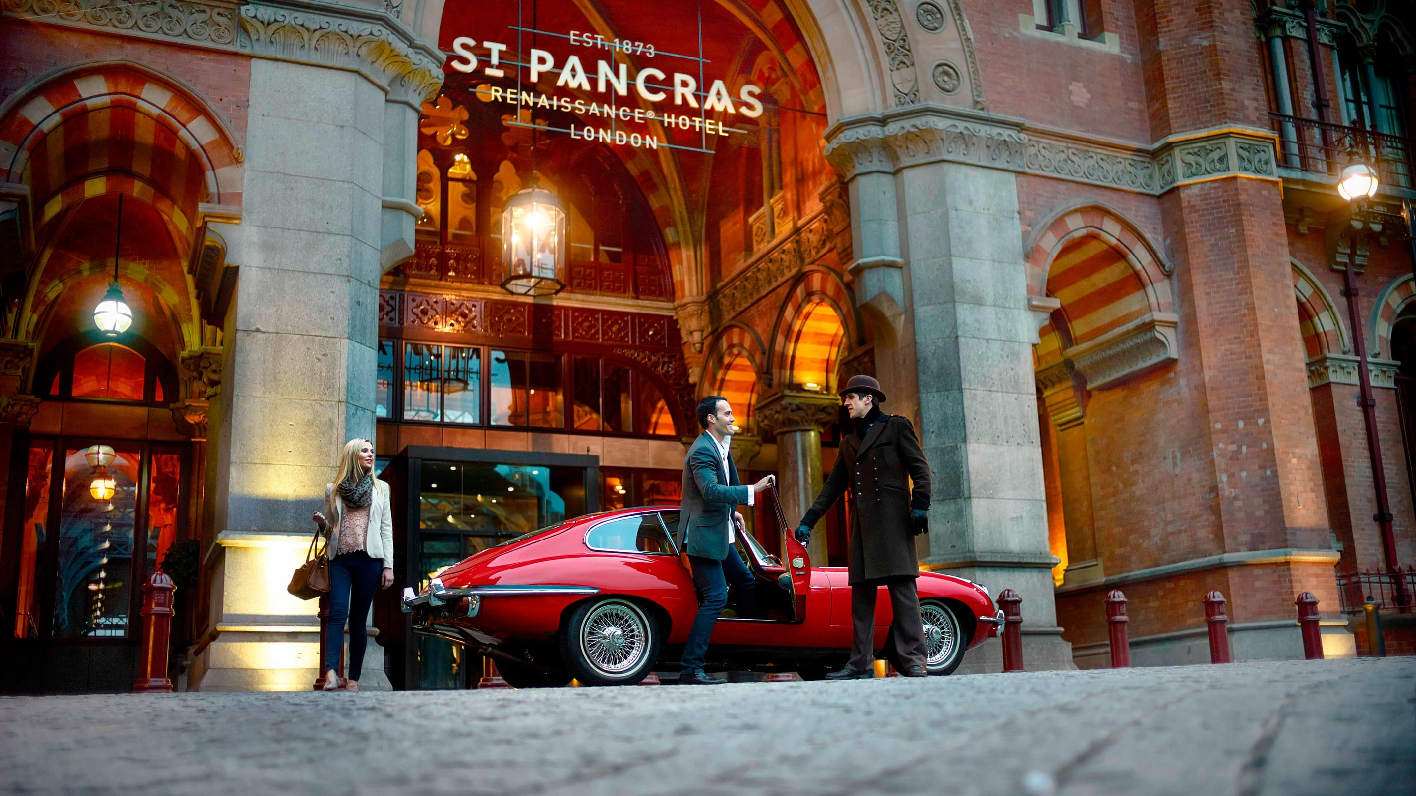 Man and woman exiting a vintage red car at the St. Pancras Hotel entrance.