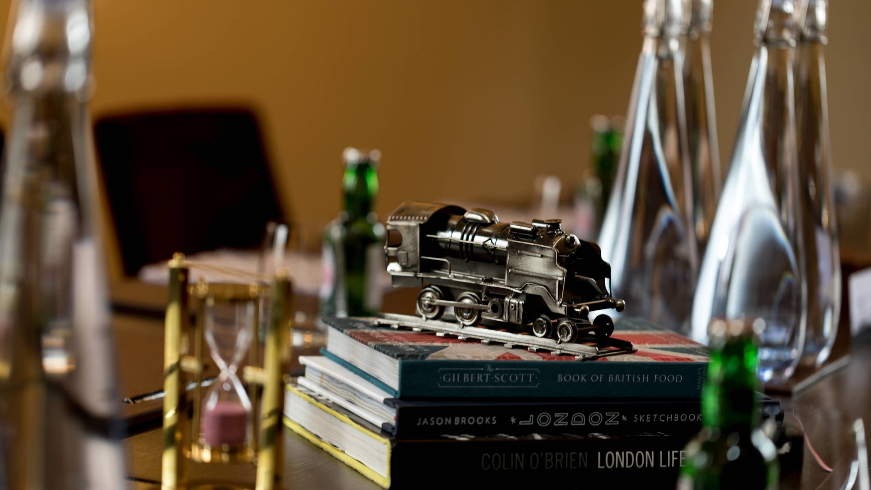 Closeup of a model train engine sitting on a stack of books.