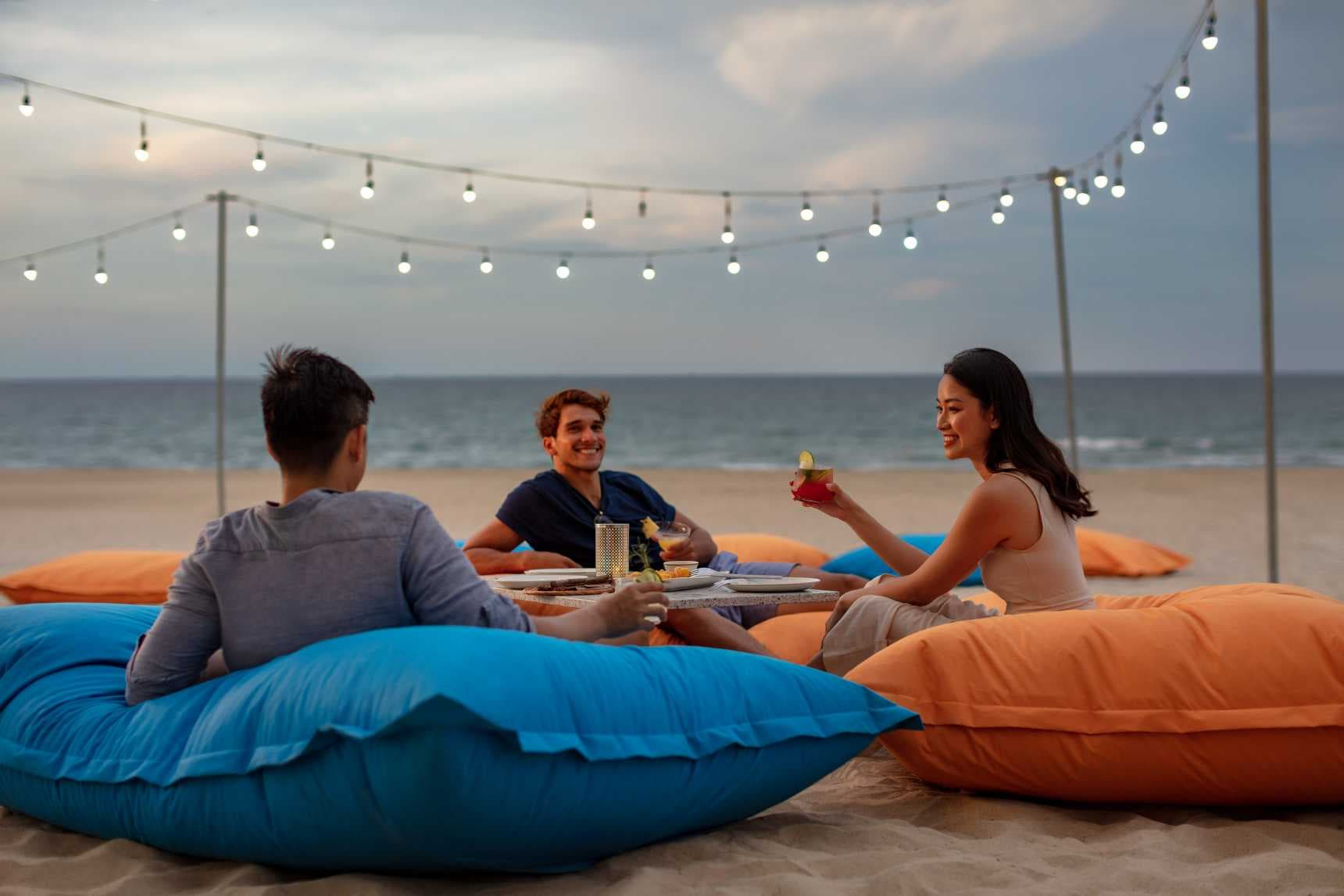 Three friends sitting on giant pillows having cocktails on the beach.