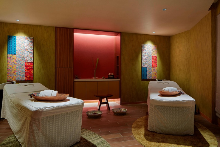 Churaku spa couples massage room with low lighting and red accents.