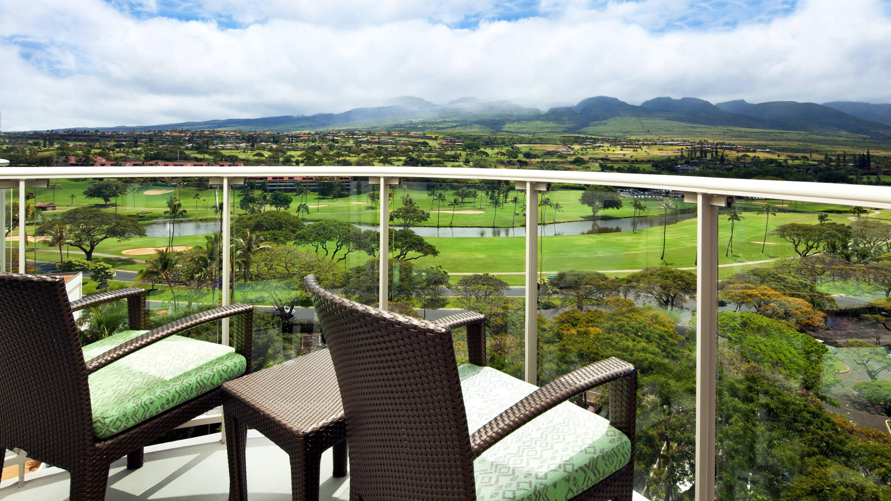 Premium Resort View guest room balcony with two chairs overlooking a golf course.