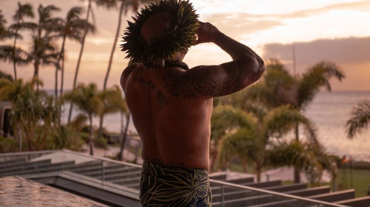 Man with leaves on his head looks into sunset.