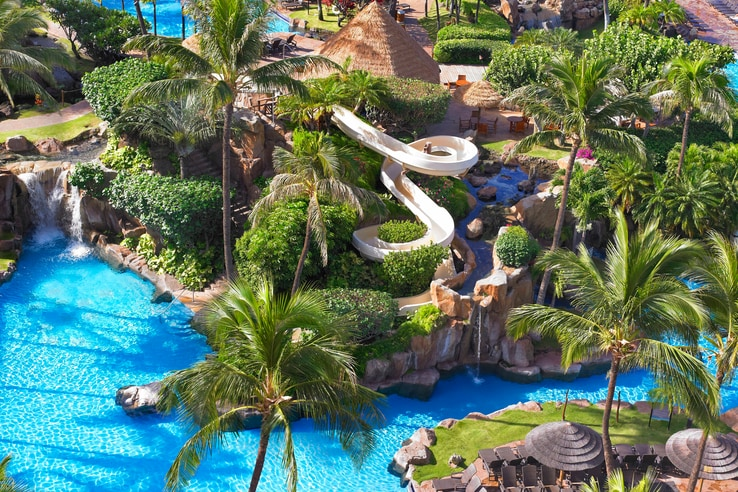 Family pool view from above with waterslide and lush vegetation.
