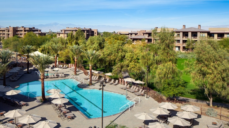 Aerial view of pool area with treeline and resort.