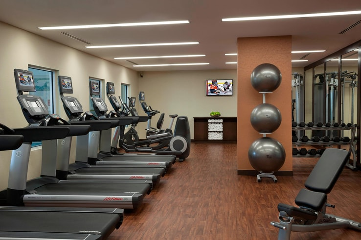 Fitness center complete with a row of treadmills, exercise balls and more.