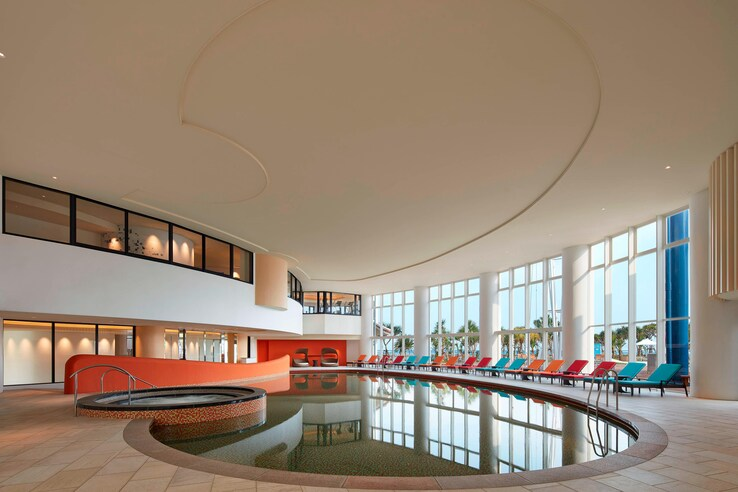 Sheraton okinawa indoor pool with floor to ceiling windows and view of the beach and sea.