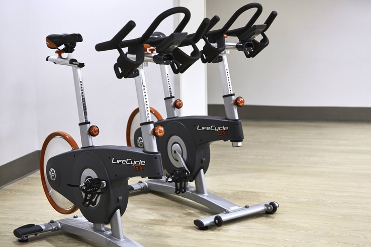Fitness bikes sitting in a pale room.