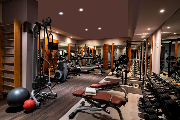 fitness room with work out equipment, machines, and benches.